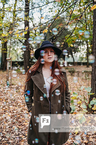 Young woman with long red hair amongst floating bubbles in autumn park  portrait