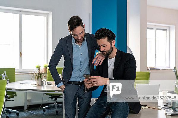 Junge männliche Geschäftskreative schauen auf Smartphone im Großraumbüro