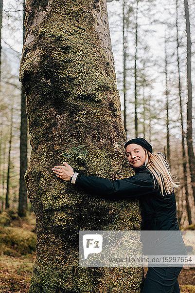 Frau umarmt Baum  Trossachs-Nationalpark  Kanada