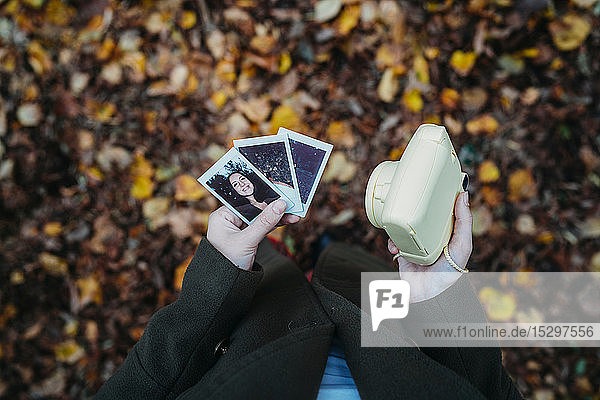 Young woman holding instant photos and camera in autumn park  overhead view
