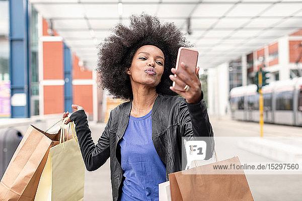 Junge Frau mit Afro-Haaren am Stadtbahnhof  die Einkaufstaschen trägt  mit spitzen Lippen für Smartphone-Selfie