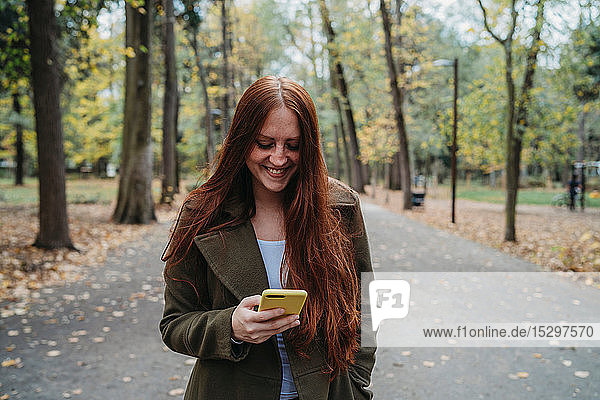 Young woman with long red hair looking at smartphone in tree lined autumn park  Florence  Tuscany  Italy