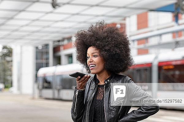 Junge Frau mit Afro-Haaren am Stadtbahnhof  spricht mit Smartphone