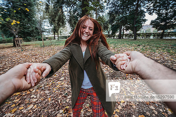 Young woman with long red hair dancing while holding boyfriend's hands in autumn park  personal perspective