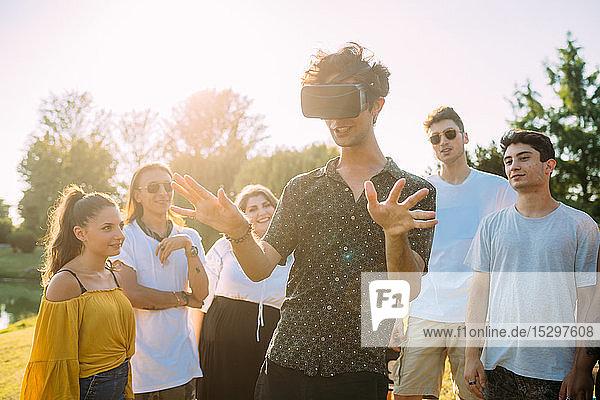 Gruppe von Freunden beobachtet Mann  der im Park in ein VR-Headset schaut