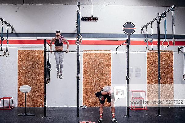 Training junger Frauen und Männer  an Übungsstangen im Fitnessstudio