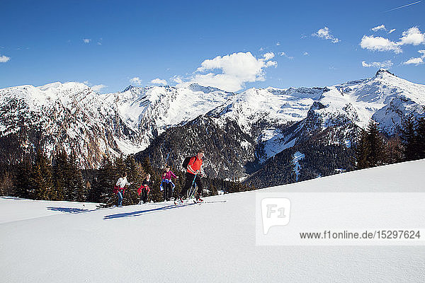 Reifes Paar und Töchter beim Schneeschuhwandern in schneebedeckter Berglandschaft  Steiermark  Tirol  Österreich