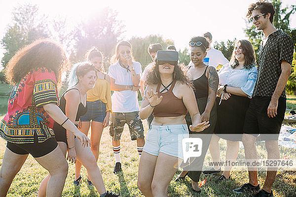 Gruppe von Freunden neckt Frau  die im Park ein VR-Headset betrachtet