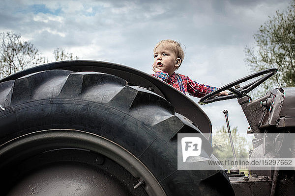 Toddler in deep thought on tractor