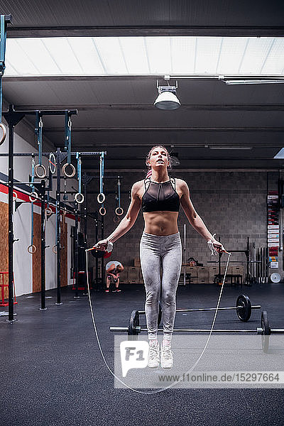 Young woman in gym skipping  full length