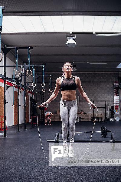 Junge Frau im Fitnessstudio beim Hüpfen  in voller Länge