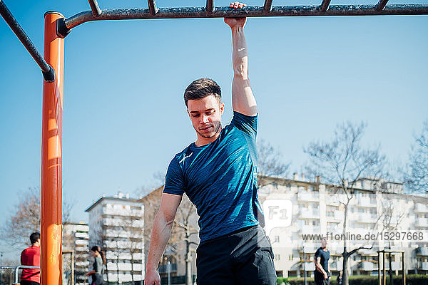 Calisthenics at outdoor gym  young man hanging by one arm from exercise equipment