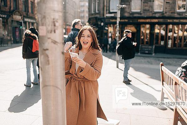 Frau mit Handy auf dem Stadtplatz  Edinburgh  Schottland