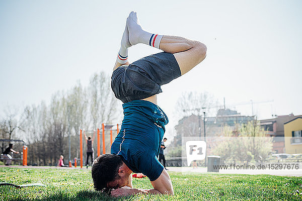 Calisthenics at outdoor gym  young man upside down in yoga position on grass