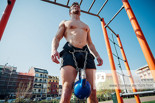 Calisthenics at outdoor gym  bare chested young man standing with kettlebell on waist harness