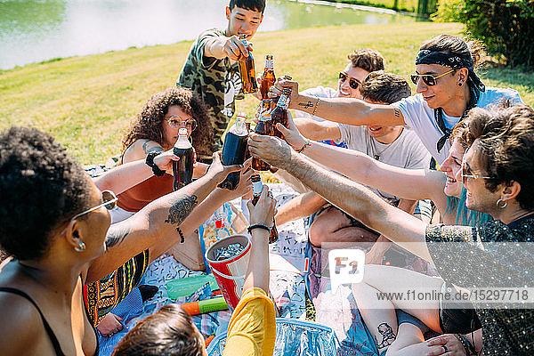Eine Gruppe von Freunden entspannt sich und trinkt beim Picknick im Park auf Erfrischungsgetränke
