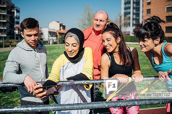 Calisthenics-Kurs im Outdoor-Fitnessstudio  Männer und Frauen beim Smartphone-Selfie