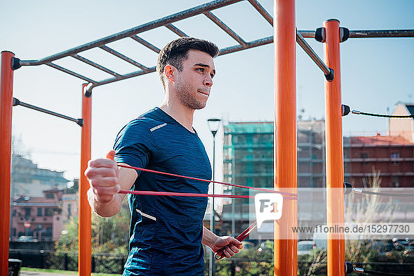Calisthenics at outdoor gym  young man stretching arms on exercise equipment