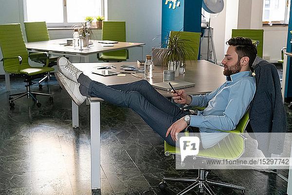 Junger männlicher Geschäftsmann kreativ mit erhobenen Füßen beim Blick auf Smartphone im Büro