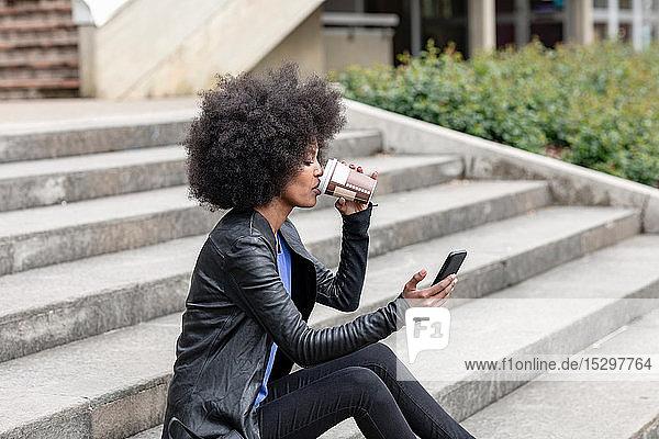 Junge Frau mit Afro-Haaren sitzt auf einer Stadttreppe  trinkt Kaffee zum Mitnehmen und schaut auf ein Smartphone