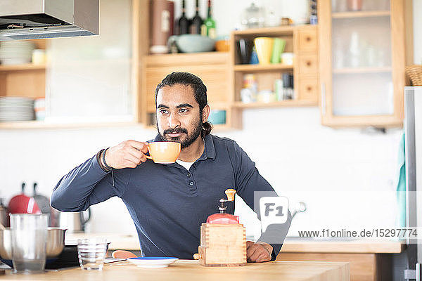 Young man at kitchen counter drinking fresh coffee