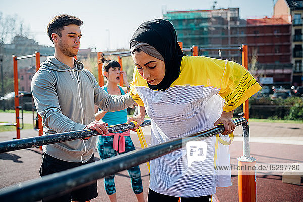 Calisthenics class at outdoor gym  male trainer encouraging young woman on parallel bars