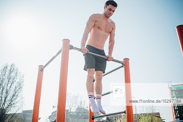 Calisthenics at outdoor gym  bare chested young man doing push up on exercise equipment