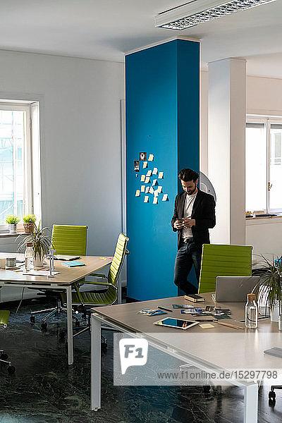 Junger männlicher Geschäftsmann kreativ schaut auf Smartphone im Großraumbüro