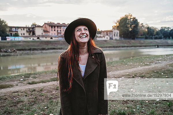 Young woman with long red hair laughing on riverside  Florence  Tuscany  Italy