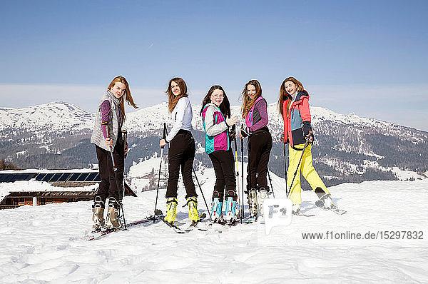 Fünf jugendliche Skifahrerinnen schauen sich in verschneiter Landschaft über die Schulter  Porträt  Tirol  Steiermark  Österreich
