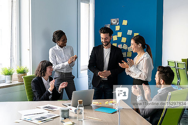 Young male and female business creative team applauding each other in office meeting