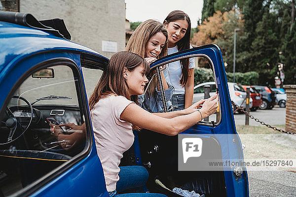 Freunde nutzen Smartphone neben dem Auto
