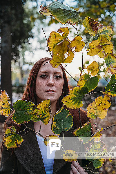 Young woman with long red hair behind twig of autumn leaves in park  portrait