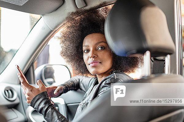 Junge Frau mit Afro-Haaren im Beifahrersitz eines Autos  die ein Smartphone hält  Porträt