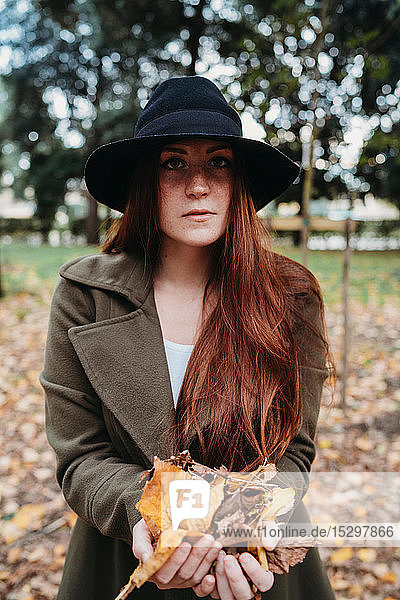 Young woman with long red hair holding autumn leaves in park  portrait