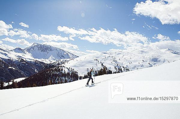Reife Frau beim Schneeschuhwandern auf schneebedecktem Berghang  Fernsicht  Steiermark  Tirol  Österreich