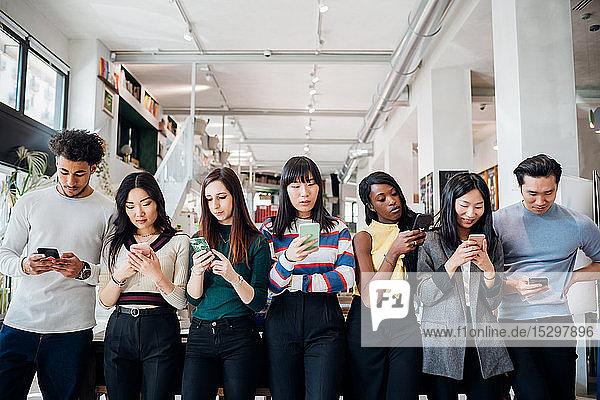 Gruppe von jungen Geschäftsfrauen und -männern in einer Reihe  die sich Smartphones anschauen
