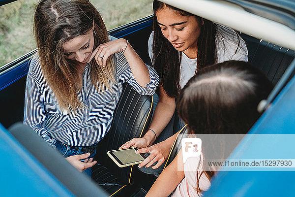 Freunde nutzen Smartphone im Auto