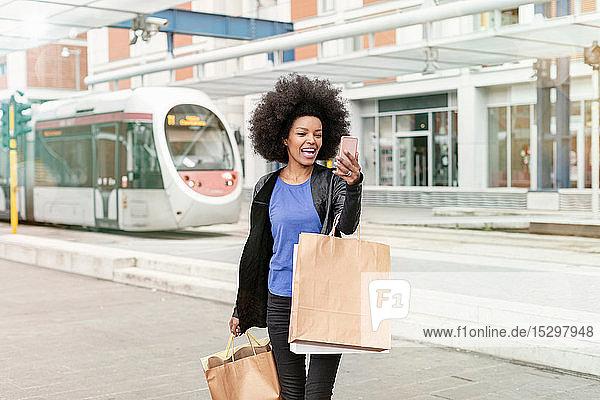 Junge Frau mit Afro-Haaren am Stadtbahnhof mit Einkaufstaschen und Smartphone-Selfie