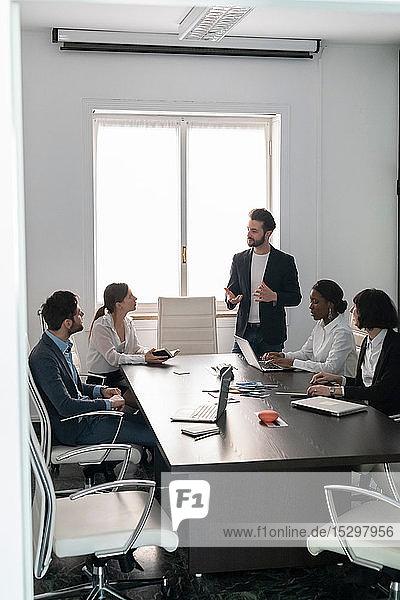 Junges weibliches und männliches Business-Kreativteam bei der Präsentation am Konferenztisch