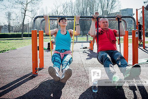 Gymnastikkurs im Freien  reifer Mann und junge Frau üben am Barren