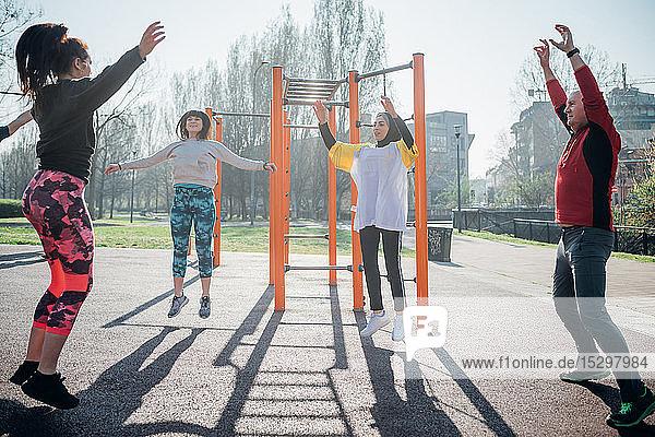 Calisthenics-Unterricht im Freiluft-Gymnastikraum  Männer und Frauen beim Springen