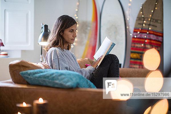 Junge Frau sitzt auf einem Wohnzimmersofa und liest ein Buch