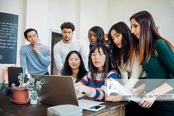 Group of young businesswomen and men looking at laptop in office meeting