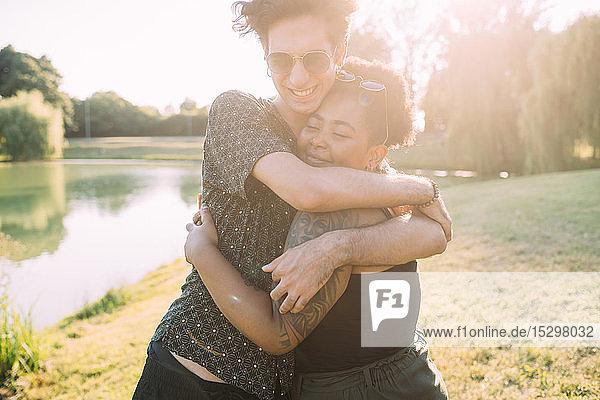 Junges Paar umarmt sich am See
