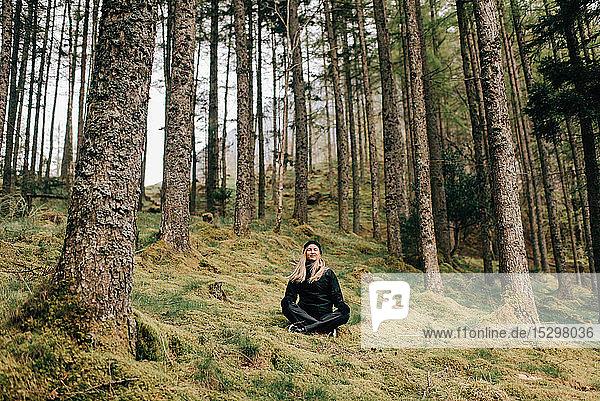Trekker meditating in forest  Trossachs National Park  Canada