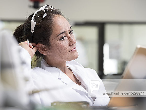 Female technician working in research laboratory in front of tablet