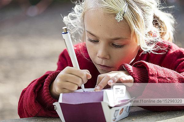 Portrait of little girl drawing on cardboard box