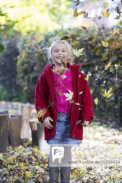 Portrait of laughing little girl throwing leaves in the air in autumn