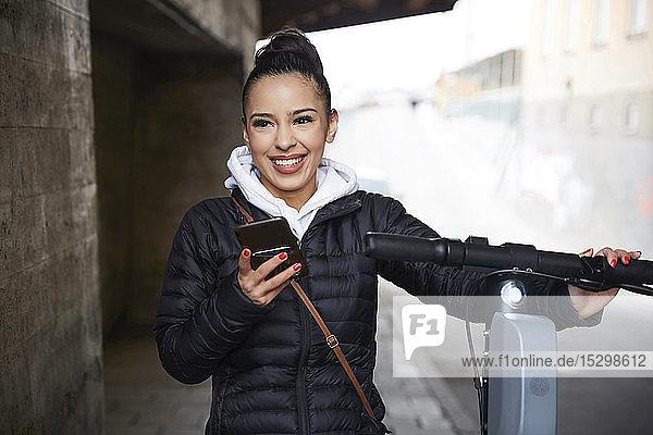 Lächelndes Teenager-Mädchen mit elektrischem Schubsroller schaut weg  während es sein Handy auf dem Gehweg hält Lächelndes Teenager-Mädchen mit elektrischem Schubsroller schaut weg, während es sein Handy auf dem Gehweg hält